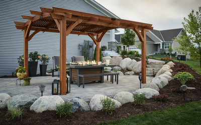 Fire table, benches, and chairs under a pergola