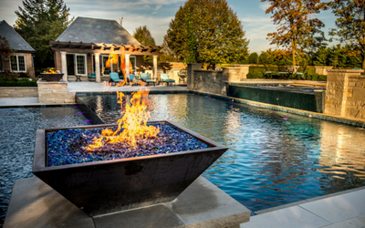A copper fire bowl with sparkling fire glass in a poolscape
