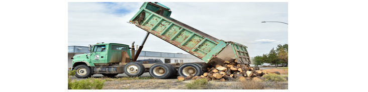 A huge truck dumping wood on the ground.