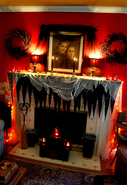 This beautiful Halloween mantel decor was done with inexpensive supplies! Between the Halloween theme and existing red wall, it's a spooky setting.