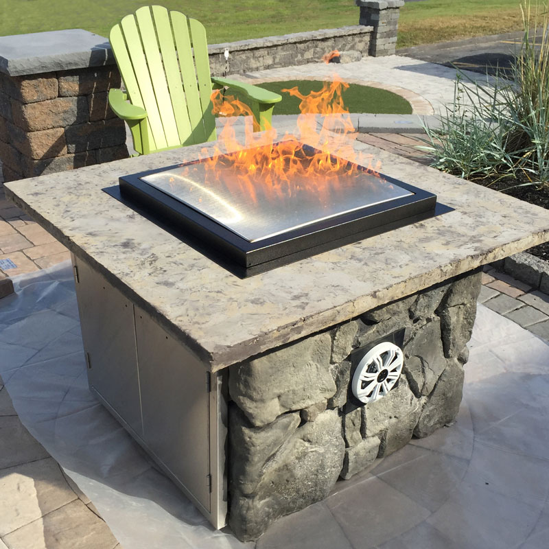 Blazing Beats All In One Fire Pit covered in Rock