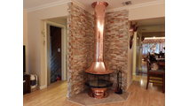 Copper spin a fire wood burning fireplace shown with copper base
