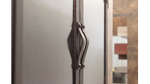 Handles on the Chesapeake masonry fireplace door are mounted on the centar bars of the cabinet doors.