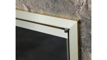 Corner detail of Huntress glass fireplace door with anodized Brushed Brass finish